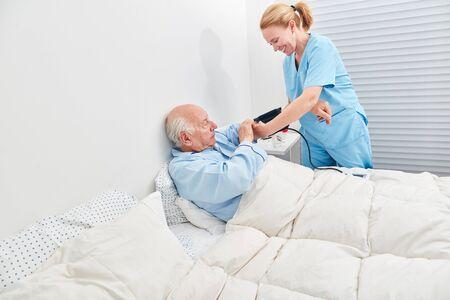 Nurse controls blood pressure of senior in bed with sphygmomanometer