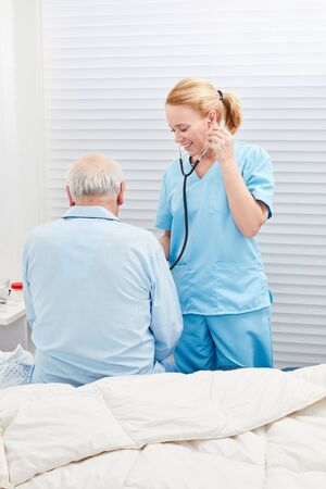 Doctor or nurse listens to patient with stethoscope in hospital Stockfoto