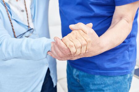 Two seniors lovingly hold hands as support and help