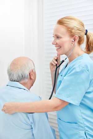 Caregiver or nurse listens to patient with stethoscope in nursing home
