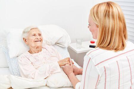 Une femme réconforte une femme âgée alitée en tant que patiente lors d'une visite à l'hôpital