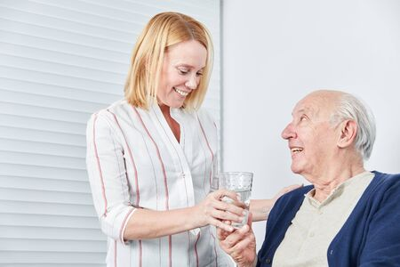 Young woman gives senior a glass of water to take the medication Stockfoto