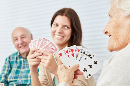 Granddaughter plays cards together with grandparents in nursing home or at home