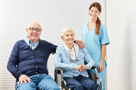 Female caregiver and a senior couple in retirement home or at home