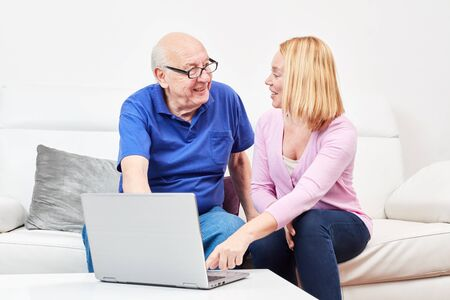 Young woman tells a senior a laptop computer and the internet Stockfoto