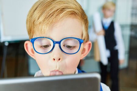 Boy at the Tablet Computer is sticking his tongue out at the video chat