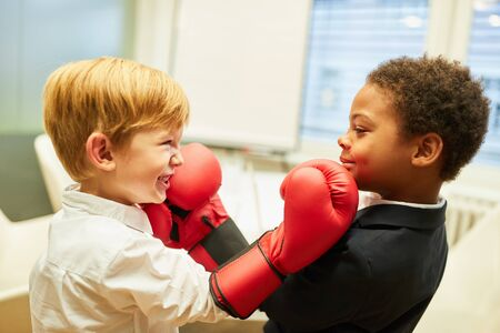 Two boys as business people with boxing gloves measure their strength