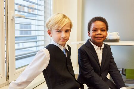 Two multicultural kids disguised as business people or managers and consultants Standard-Bild