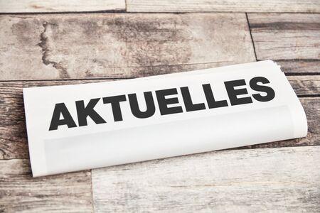 "Folded newspaper with German word ""Aktuelles"" (news) as headline lies on wood"