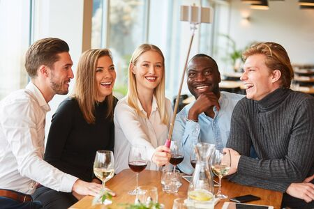 Multicultural group of young people is making selfie in restaurant with selfie stick