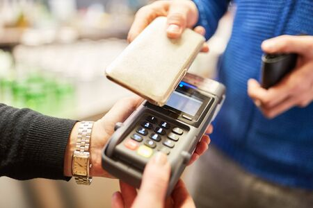 Customer pays contactlessly with smartphone via NFC on reader in retail