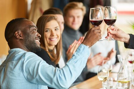 African man toasting with glass of red wine in restaurant with friends 版權商用圖片