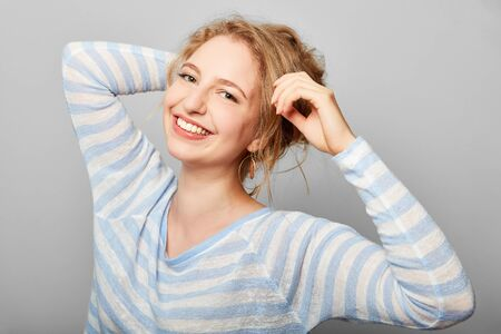 Laughing young blond woman is happy and looking into the camera