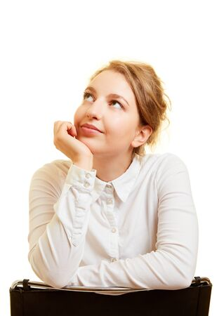 Young woman looks up dreamily while thinking