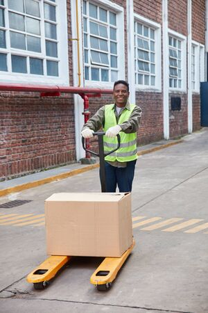 African logistics worker carries a package on the pallet truck