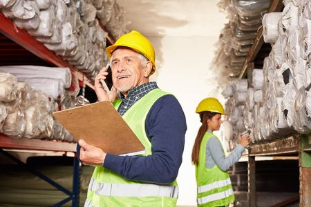 Senior warehouse worker in transit phoning with smartphone in warehouse