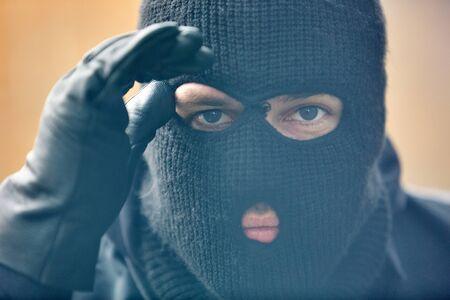 La police SEK Einsatzkraft avec un masque anti-tempête regarde à travers une fenêtre dans une maison Banque d'images