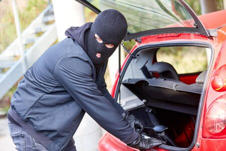 Thief steals a purse from the trunk of a car Stock Photo