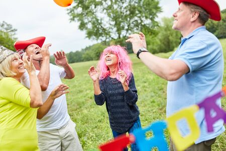Group of seniors celebrate and play in colorful costumes at a birthday party