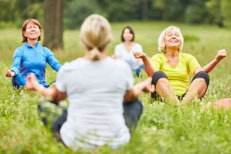 Group of women together while meditating in a yoga class in nature