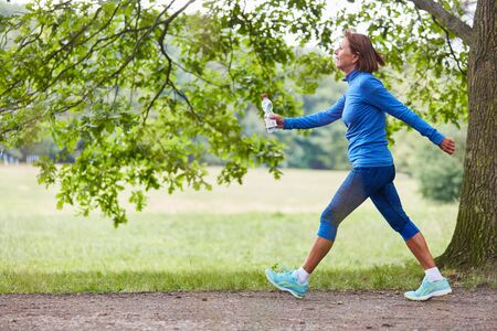 Vital senior woman walking in nature trains endurance and fitness