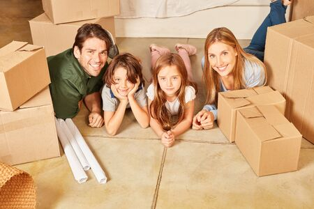 Happy family with two kids in new condo between cartons