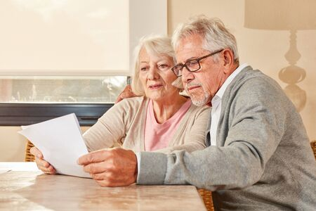Senior couple reading together a retirement plan or insurance contract 免版税图像