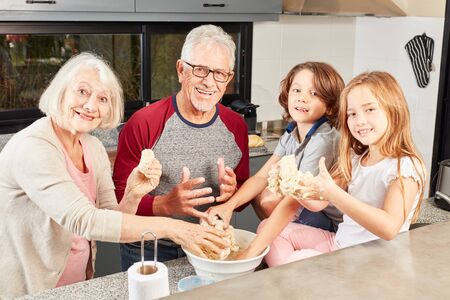 Family with grandparents and grandchildren at the dough knead together in the kitchen