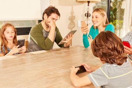 La famille est assise avec un smartphone et une tablette à la table