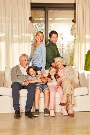 Heureuse famille élargie avec grands-parents et enfants sur le canapé d'un appartement pour personnes âgées