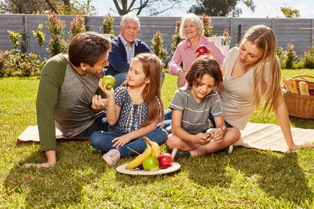 Extended family with children and grandparents is eating fruit at the picnic in summer in the garden