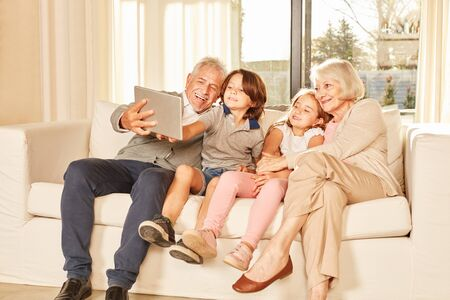 Grandchildren and grandparents on the sofa take a selfie with the Tablet PC 写真素材