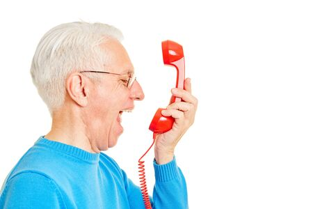 Old man angrily roars in a red telephone receiver Stock Photo