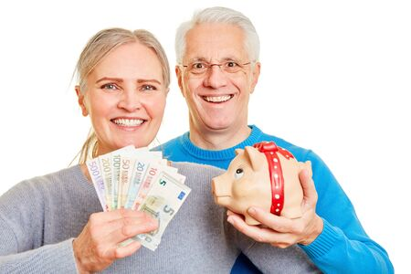 Laughing senior couple with euro money and piggy bank
