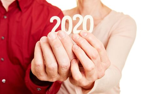Two seniors hands holding the number 2020 for the year