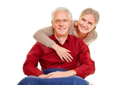 Old smiling woman hugs her senior man in wheelchair