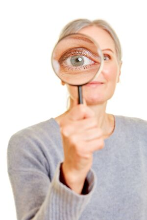 Old woman is holding magnifying glass in front of her eye for control 写真素材