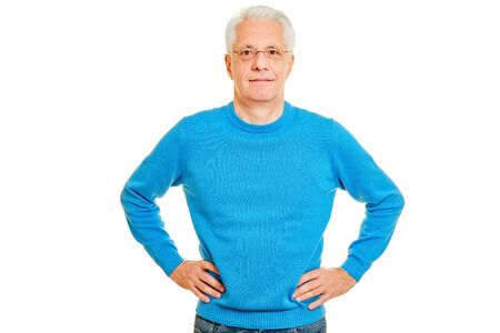 Senior man is smiling head-on with hands on hip