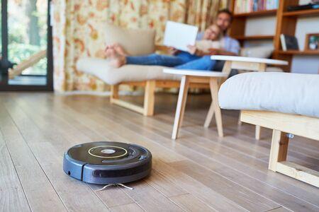 Vacuum cleaner vacuuming on floor in living room