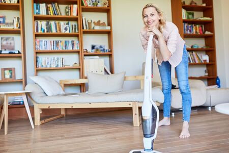 Housewife in the living room draws on vacuum cleaner while parquet vacuuming