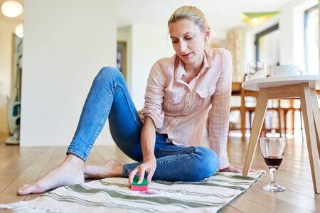 Housewife removes with home remedies the red wine stains from the living room carpet