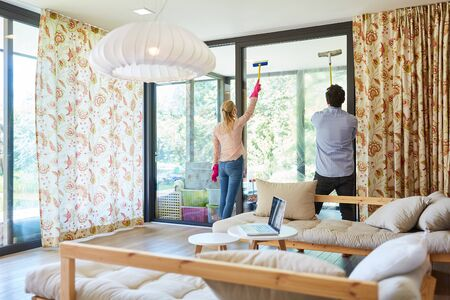 Young couple in streak-free window cleaning together in the living room