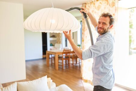 Houseman with vacuum cleaner vacuuming on ceiling lamp in the living room