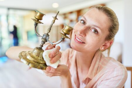 Cleaning lady cleans and polishes brass candle holders during spring cleaning Imagens