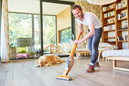 Smiling houseman at the parquet floor vacuuming the living room 스톡 콘텐츠