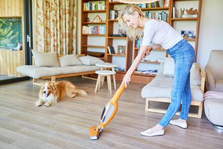 Housewife as a cleaner with vacuum cleaner at the parquet floor vacuuming Stock Photo