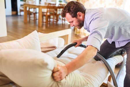 Houseman with vacuum cleaner vacuuming the sofa in the living room Stock Photo