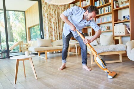 Hausmann cleans parquet floor in the living room with the vacuum cleaner