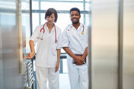 African nurse and asian nurse together in the elevator