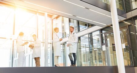 Modern hospital with doctors and nurses in the corridor while talking